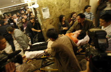 A family member of a passenger aboard Malaysia Airlines MH370 is rushed to an ambulance after she collapsed, in the Lido hotel in Beijing