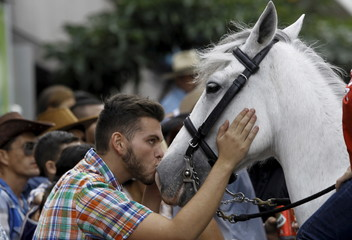 A man kisses a horse during a traditional horse parade through the streets of San Jose
