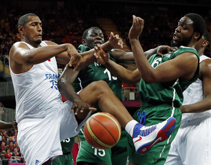 France's Diaw, Nigeria's Oyedeji and Diogu reach for the rebound during their men's preliminary round Group A basketball match at the Basketball Arena during the London 2012 Olympic Games