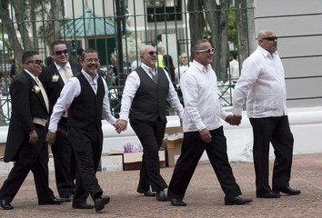 Couples hold hands while walking to their wedding in San Juan