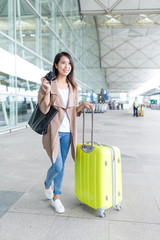 Woman taking photo with digital camera in airport