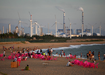 Windmills and a power plant can be seen in the distance as beachgoers watch sunset in the city of Dongfang on the western side of China's island province of Hainan