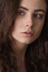 Dramatic portrait of a young beautiful brunette girl with long curly hair in the studio.