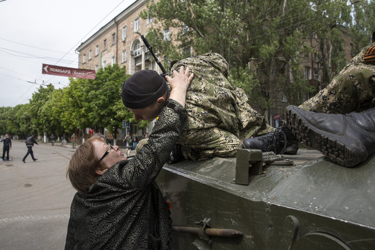 A woman gives a kiss to an armed Pro-Russia man riding an armoured personnel carrier during celebrations to mark Victory Day in Slaviansk