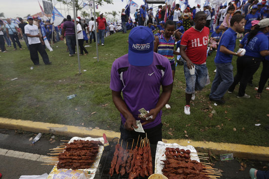 Street vendor, who also supports Juan Carlos Navarro, sells meat on sticks while wearing Navarro cap before Navarro, presidential candidate of the Democratic Revolutionary Party, makes a speech at the closing campaign rally in Panama City