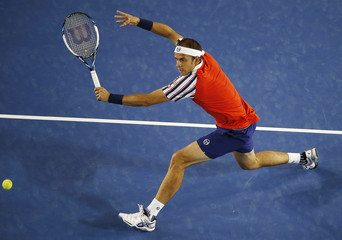 Muller of Luxembourg hits a return to Djokovic of Serbia during their men's singles match at the Australian Open 2015 tennis tournament in Melbourne