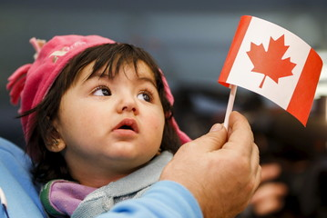 A young Syrian refugee looks up as her father holds her and a Canadian flag at the as they arrive at Pearson Toronto International Airport in Mississauga
