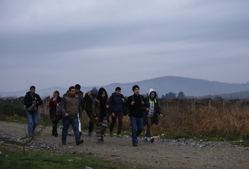 Migrants walk after crossing the border from Greece into Macedonia, near Gevgelija