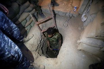 A member of the Shi'ite Badr Organisation fighter inspects a tunnel used by Islamic State militants during a battle with Islamic State at the airport of Tal Afar west of Mosul