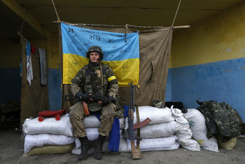 A Ukrainian serviceman sits at a checkpoint during a POWs exchange near Luhansk, eastern Ukraine