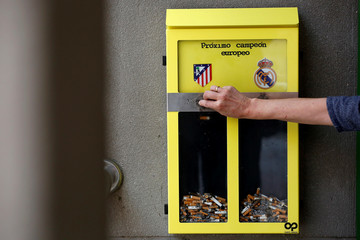 Real Madrid and Atletico Madrid logos are seen on a public ashtray