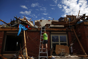 Tamera Wirick climbs a ladder to her aunt's destroyed apartment building in Joplin, Missouri
