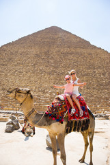 Tourists woman and girl are riding a camel in the background of the pyramids in Egypt