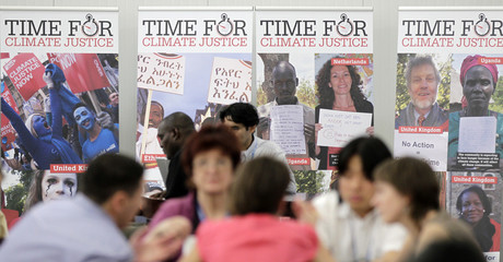 """People stand next to posters reading """"Time for Climate Justice"""" in Cancunmesse, where climate talks are taking place, in Cancun"""