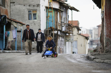 Men walk a long a street as a Syrian refugee girl plays in the Hacibayram district of Ankara