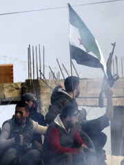 Members of the Free Syrian Army shout slogans against Syrian President Bashar al-Assad while holding a Syrian opposition flag as gunfire is heard, as seen from the Turkish border town of Ceylanpinar