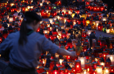 A girl lights a candle on a square near the Presidential Palace in Warsaw