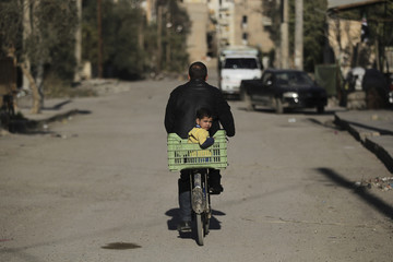 A child rides on the back of a bicycle through a damaged street in Deir al-Zor, eastern Syria