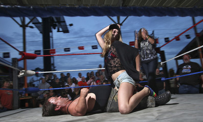 A woman performs with wrestler Joe Kidd during a competition at the biker bar Suck Bang Blow in Murrells Inle