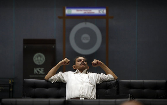 A man stretches himself as he sits on a couch in front of a ceremonial gong at Karachi Stock Exchange