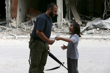 A girl talks to an armed gunman in Jobar, a suburb of Damascus, Syria