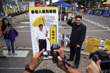 Howard, a 35-year-old Australian Chinese musician and lookalike of North Korean leader Kim Jong Un, stands by a poster featuring a manipulated photo of Chinese President Xi Jinping in part of Hong Kong's financial central district occupied by pro-democracy