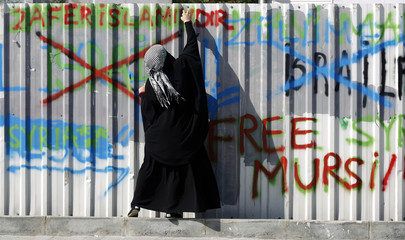 A pro-Palestinian demonstrator sprays graffiti during an anti-Israeli protest outside the Justice Palace in Istanbul