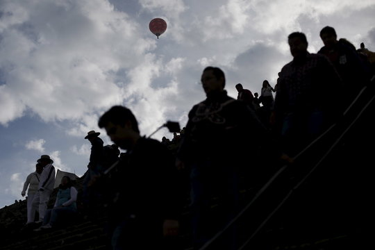 A hot air balloon floats above people standing in line to climb the Pyramid of the Sun and welcome the spring equinox in the pre-hispanic city of Teotihuacan, on the outskirts of Mexico City