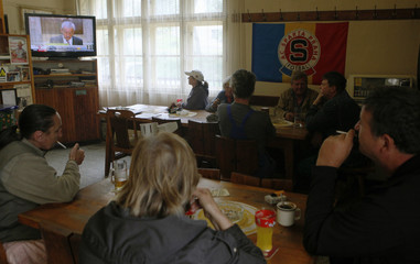 Local customers of a small pub in the village of Oubenice watch the live TV broadcast of Czech Republic's Health Minister Heger's news conference
