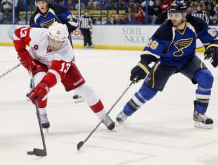 Detroit Red Wings Pavel Datsyuk and St. Louis Blues Carlo Colaiacovo fight for the puck during the third period of their NHL hockey game in St. Louis