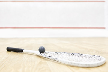 one squash racket and ball