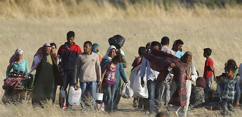 Syrian Kurds from Kobani walk to the border fences as they are pictured from the Turkish border town of Suruc in Sanliurfa province, Turkey