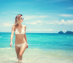Beautiful young woman in a white bikini walking along a tropical beach with azure water and white sand