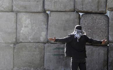 A protester gestures in front of barricades placed by the Egyptian military at cabinet offices near Tahrir Square in Cairo