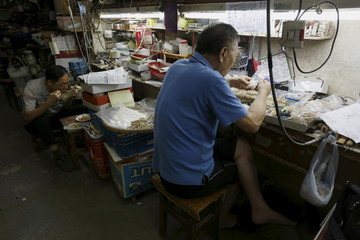 A worker put beads made from mammoth tusks into plastic bags, beside another worker eating lunch inside a carving and jewellery factory in Hong Kong