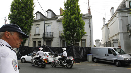 French police stand guard outside the house where a human body part was found in Nantes