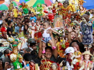 A devotee carries his child to be blessed by the lay minister with holy water during the annual feast of Sto. Nino in Manila