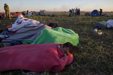 A migrant rests in a sleeping bag in a makeshift camp at a collection point in the village of Roszke
