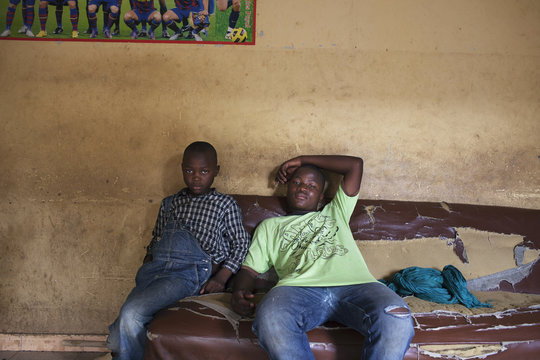 Boys sit on a couch at a barbershop in Gao