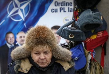 A street vendor sells Soviet Union military uniforms in front of a pre-election poster for the Liberal Party in Chisinau