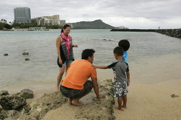 Shu and his family play at the beach as Tropical Storm Iselle passes through the Hawaiian islands, in Honolulu, Hawaii