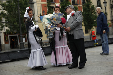A man dressed in Madrid's traditional attire shows his companions an umbrella with an image of a famous painting by the Spanish artist Goya during celebrations for San Isidro in Madrid