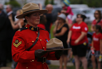 A Royal Canadian Mounted Police officer carries a hat belonging to one of the fallen officers during a funeral procession for three fellow officers who were killed last week in Moncton