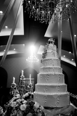 Wedding cake and candle with flower decorate on restaurant interior background for wedding party. monotone color