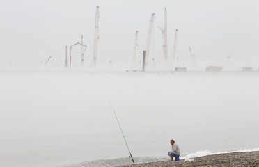A man fishes, with a new port under construction seen in the background, in the Russian Black sea town of Sochi,