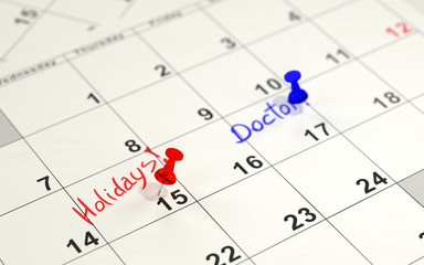 Red and blue pins marking the important days on a calendar