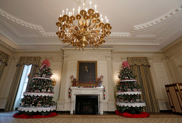 Christmas trees flank a painting of Abraham Lincoln at the State Dining Room during a preview of holiday decor at the White House in Washington