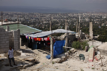 A Haitian boy stands next to his house which was destroyed by the January 2010 earthquake in Port-au-Prince