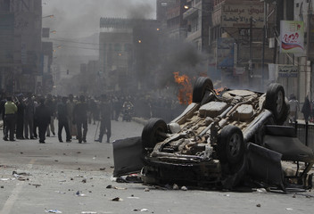 Police block people from reaching a car belonging to government supporters outside Sanaa University