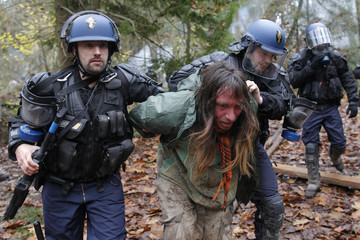 French riot gendarmes detain a demonstrator as evacuation operations continue on land that will become the new airport in Notre-Dame-des-Landes